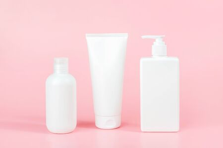 Set of care cosmetic for skin, body or hair. Three white blank cosmetics bottles, tube on pink background. Spa Cosmetic Beauty Concept. Front view Mockup.