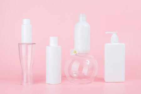 Set of care cosmetic for skin, face, body or hair. White blank cosmetics bottles and tube on glass podiums, pink background. Spa Cosmetic Beauty Concept. Front view Mockup.