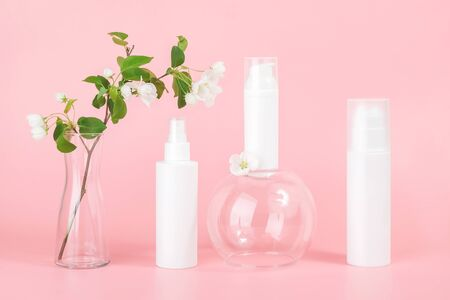 Set of cosmetic for skin care face, body. White blank cosmetics bottles and tube on glass podium and flowering branch in vase, pink background. Natural Organic Spa Cosmetic Beauty Concept Mockup.