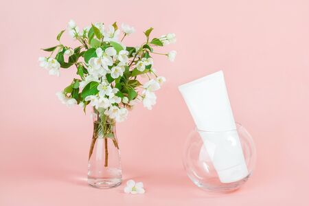 One white blank cosmetic tube bottle and blooming branch in vase on pink background. Natural Organic Spa Cosmetic Beauty Concept. Mockup Front view. Standard-Bild