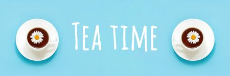 Tea time text and two white cup of tea with chamomile on dish saucer, blue background. Top view Flat lay Banner.