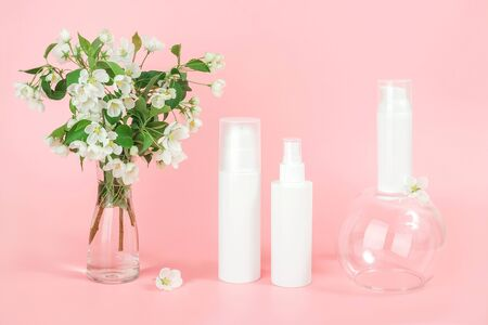 Set of cosmetic for skin care face, body. White blank cosmetics bottles and tube on glass podium and flowering branch in vase, pink background. Natural Organic Spa Cosmetic Beauty Concept Mockup. Banco de Imagens - 150090968