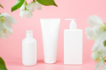 Set of care cosmetic for skin, body or hair. Three white blank cosmetics bottles, tube framed by flowers on pink background. Spa Cosmetic Beauty Concept. Front view Mockup. Standard-Bild