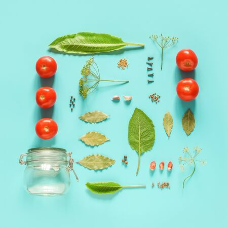 Pickled tomatoes. Ingredients for marinated tomatoes and glass jar on blue background. Concept culinary recipe preservation of vegetables in harvest season. Creative flat lay Top view Copy space. Standard-Bild - 150432360