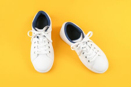 White sports shoes, sneakers with shoelaces on a yellow background. Sport lifestyle concept Top view Flat lay Copy space. Standard-Bild - 150101073