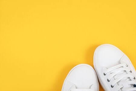 White sports shoes, sneakers with shoelaces on a yellow background. Sport lifestyle concept Top view Flat lay Copy space. Standard-Bild - 150103353