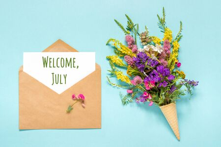Welcome July text on paper card in craft envelope and bouquet field colored flowers in waffle ice cream cone on blue background. Creative Flat Lay Top view. Concept Hello July. Standard-Bild