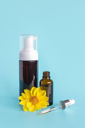 Essential oil in small open brown dropper bottle with lying glass pipette, big bottle with white dispenser and yellow flower on blue background. Concept natural organic beauty cosmetics product. Standard-Bild