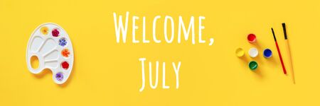 Welcome July text. Colorful flowers on artistic palette, brush, gouache on yellow background. Creative concept Hello summer. Top view Flat lay Banner. Standard-Bild - 150526705
