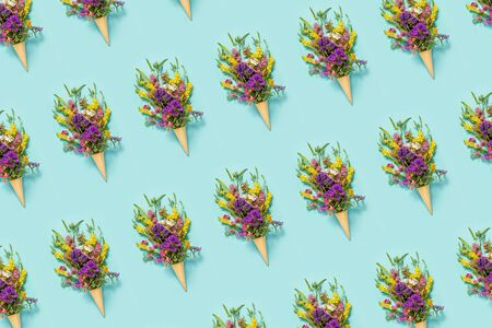 Flower pattern. Bouquet field colored flowers in waffle ice cream cone on blue paper background Creative Flat Lay Top view. Banco de Imagens - 150263421
