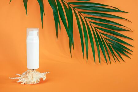 One white blank cosmetics bottle with sunscreen, suncream or other cosmetic product, seashell and green brunch palm on orange background. Concept skin care in summer holiday Mockup Front view. Standard-Bild