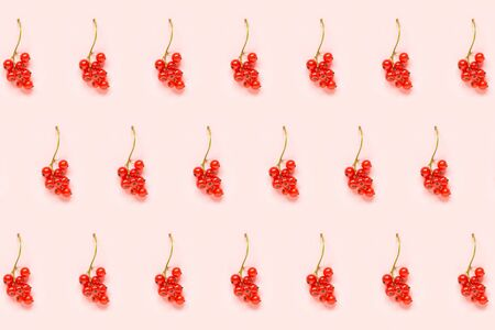 Berry pattern. Twigs of red currant berry on pink paper background. Minimal style Creative Flat lay Top view.