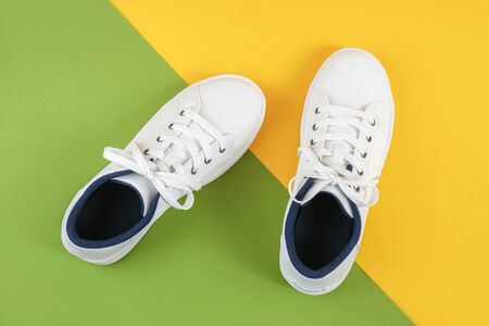 White sports shoes, sneakers with shoelaces on a green and yellow background. Sport lifestyle concept Top view Flat lay. Banco de Imagens - 150459898