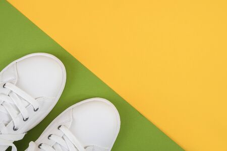 White sports shoes, sneakers with shoelaces on a green and yellow background. Sport lifestyle concept Top view Flat lay. Banco de Imagens - 150459752