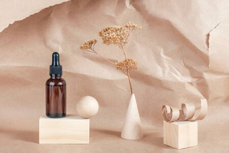 Serum, essential oils or fluid collagen in brown glass bottle with pipette, wooden geometric shapes and dried flowers on beige paper background. Natural Organic Spa Cosmetic Beauty concept.