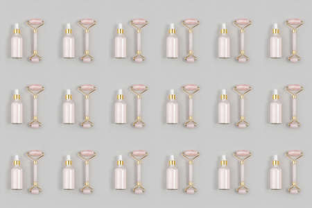 Cosmetic pattern. Crystal rose quartz facial roller and anti-aging collagen, serum in glass bottle on grey background. Facial massage for natural lifting, Beauty concept Top view Flat lay.