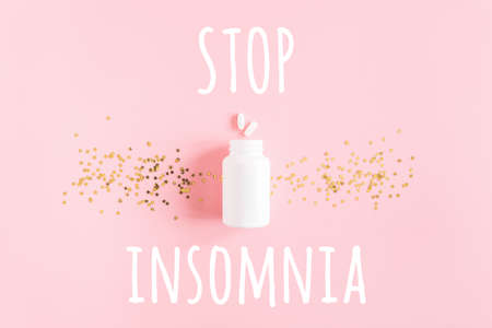 Stop insomnia text, two pills, white bottle and gold stars confetti on pink background. Concept Insomnia and sleep problems. Top view Flat lay.