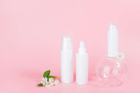 Set of cosmetic for skin care face, body. White blank cosmetics bottles and tube on glass podium and flowering branch, pink background. Natural Organic Spa Cosmetic Beauty Concept Mockup.