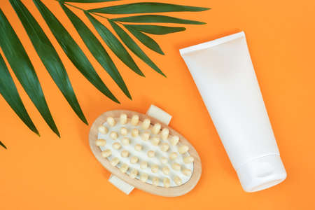 White blank cosmetic tube of cream or body lotion and wooden anti-cellulite massager, palm leaf on orange background. Concept fight against cellulite. Mockup Front view Copy space.