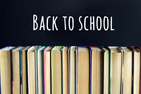 Back to school text on black chalkboard background and stack of books . Concept education. Front view.