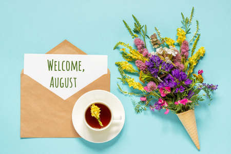 Welcome August text on paper card in craft envelope, cup of tea and bouquet field flowers in waffle ice cream cone on blue background. Creative Flat Lay Top view. Concept Hello August.