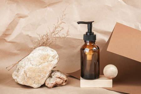 Brown glass bottle with pump of cosmetic products on wooden geometric shapes, stones and dried flowers on beige paper background. Natural Organic Spa Cosmetic Beauty concept Front view Mockup.