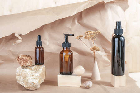 Brown glass bottles of cosmetic products on stone, wooden geometric shapes and dry flowers on beige paper background. Natural Organic Spa Cosmetic Beauty concept Front view Mockup.