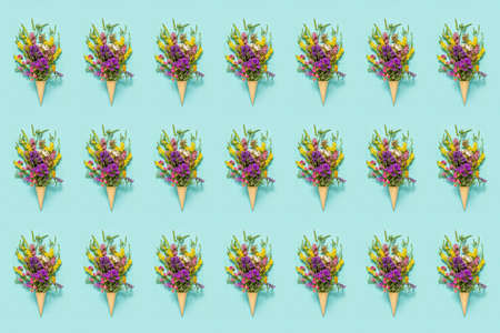 Flower pattern. Bouquet field colored flowers in waffle ice cream cone on blue paper background Creative Flat Lay Top view. Banco de Imagens - 151338470