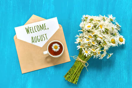 Welcome August text on white card in craft envelope, bouquet white chamomiles flowers and cup of tea on blue background. Concept Hello august. Greeting card Flat Lay.