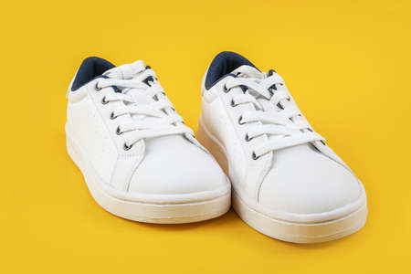 White sports shoes, sneakers with shoelaces on a yellow background. Sport lifestyle concept Top view Flat lay. Stock fotó