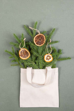 A bouquet of fir branches with circles of dried oranges in fabric eco bag on green background. Concept eco-friendly and zero waste. Top View Flat lay.
