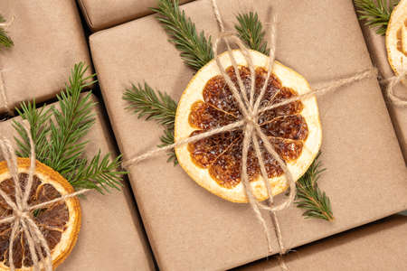 Christmas or New Years pattern from boxes in craft paper with dried oranges, spruce branches and twine close-up. Concept Zero waste, eco friendly Merry Christmas. Top view Flat lay. Zdjęcie Seryjne
