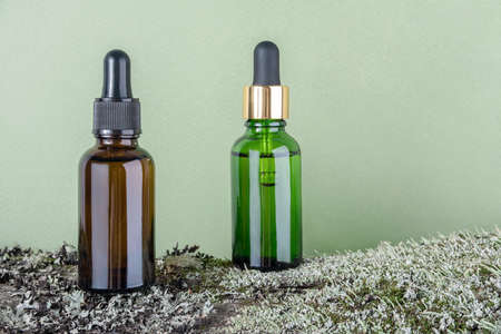 Two brown, green glass bottles with serum, essential oil or other cosmetic product on tree bark covered with moss against green background. Natural Organic Spa Cosmetic Beauty concept.