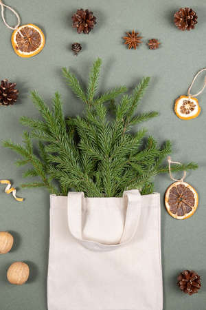 Bouquet of fir branches in fabric eco bag and eco-friendly natural decor on green background. Concept christmas zero waste. Top View Flat lay. 免版税图像