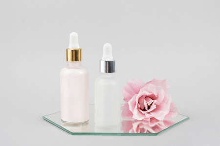 Two glass bottles with serum, essential oil or other cosmetics product and beautiful pink flowers on mirror on gray background. Natural Organic Spa Cosmetic Beauty concept Front view.