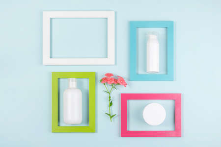 Set of cosmetics for skin care face, body, hands. White blank cosmetic bottle, tube, jar, one flower and bright frames on blue background. Creative Cosmetic Beauty Concept. Copy space MockupTop view. 免版税图像