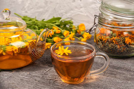 Cup of herbal tea, transparent teapot and marigold flowers on wood background. Calendula Tea Benefits Your Health concept. Front view. 免版税图像