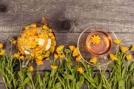 Cup of herbal tea and transparent teapot and marigold flowers on wood background. Calendula Tea Benefits Your Health concept. Top view. 免版税图像
