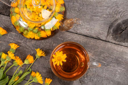 Cup of herbal tea and transparent teapot and marigold flowers on wood background. Calendula Tea Benefits Your Health concept. Top view Copy space. 免版税图像
