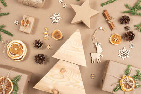 Xmas composition. Homemade wooden Christmas tree, gifts, holiday decor on craft beige background, closeup. Concept christmas zero waste, eco-friendly. Top view Flat lay Copy space.