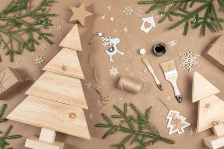 XMAS or New Year composition. Wooden Christmas trees, paint, brushes and fir branches on craft beige background. Concept Zero waste, eco - friendly Merry Christmas. Top view Flat lay.