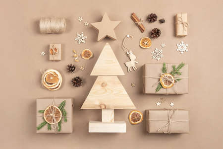 Xmas composition. Homemade wooden Christmas tree, gifts, holiday decor on craft beige background. Concept christmas zero waste, eco-friendly. Top view Flat lay. 免版税图像
