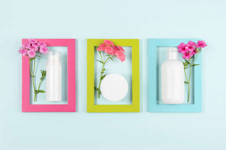 Set of cosmetics for skin care face, body, hands. White blank cosmetic bottle, tube, jar, flowers in bright frames on blue background. Creative Cosmetic Beauty Concept. Mockup Top view. 免版税图像