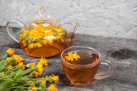 Cup of herbal tea and transparent teapot and marigold flowers on wood background. Calendula Tea Benefits Your Health concept. Copy space. Zdjęcie Seryjne