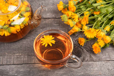 Cup of herbal tea and transparent teapot and marigold flowers on wood background. Calendula Tea Benefits Your Health concept. Zdjęcie Seryjne