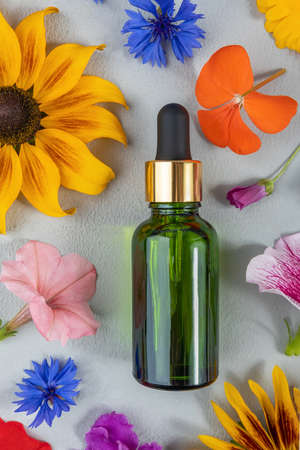 Anti-aging collagen, facial serum or other cosmetic product in green glass bottle among the colored flowers on gray background. Natural Organic Spa Cosmetic concept Mockup Top view.