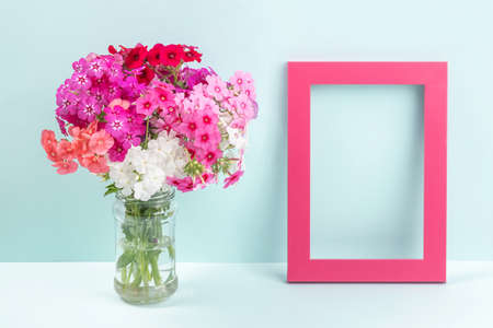 Bouquet of bright colored flowers in vase and wooden empty frame on table against the background of blue wall. Template for greeting card, invitation. Mockup Copy space Front view. 免版税图像