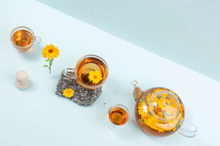Cup of herbal tea and transparent teapot with calendula flowers on blue background. Calendula Tea Benefits Your Health concept. Top view Flat lay.