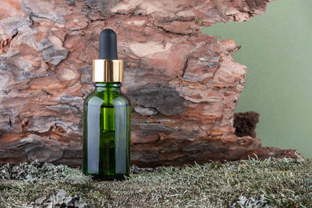 One green glass cosmetic bottles with serum, essential oil on green moss and tree bark background. Natural Organic Spa Cosmetic concept Front view.