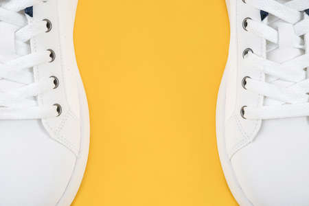 Two white sports shoes, sneakers with shoelaces on the edges of the yellow background with copy space. Sport lifestyle concept Top view Flat lay Close-up.